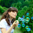Young girl blowing soap bubbles in autumn park -  