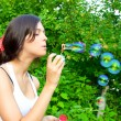Young girl blowing soap bubbles in autumn park — Stock Photo #5330023
