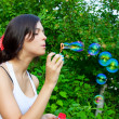Young girl blowing soap bubbles in autumn park - Foto Stock