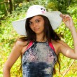 Cute brunette girl in the white hat outdoor - Stock Photo