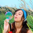Young girl blowing soap bubbles in autumn park — Stock Photo #5330111
