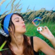 Young girl blowing soap bubbles in autumn park — Stock Photo