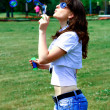Young girl blowing soap bubbles in autumn park — Stock Photo #5330378