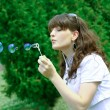 Young girl blowing soap bubbles in autumn park — Stock Photo #5330381