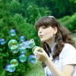 Young girl blowing soap bubbles in autumn park — Stock Photo #5330384