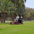Worker on a riding lawn mower cutting the grass — Stok fotoğraf