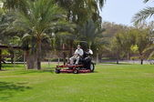 Worker on a riding lawn mower cutting the grass — Foto de Stock