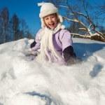 Little girl sliding in the snow — Stock Photo
