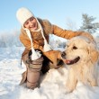 Happy woman playing with golden retriever outdoors - Stock Photo