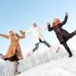 Happy girls jumping in the snow — Stock Photo #5310836