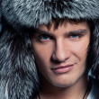 Portrait of handsome young man wearing fluffy hat — Stock Photo