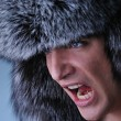 Photo: Portrait of handsome young man wearing fluffy hat