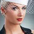 Stock Photo: Beautiful young woman in white hat with net veil. Retro portrait