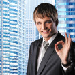 Happy businessman against his office building — Stock Photo