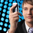 Stock Photo: Young businessman holding mobile phone over abstract background