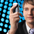 Young businessman holding mobile phone over abstract background — Stock Photo #5310937