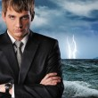 Seriour businessman over dark stormy sky — Stockfoto