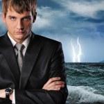 Seriour businessman over dark stormy sky — Stock Photo