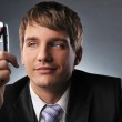 Young businessman holding mobile phone — Stock Photo