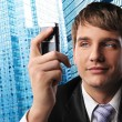 Royalty-Free Stock Photo: Young businessman with a mobile phone against his office building