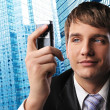 Young businessman with a mobile phone against his office building - Stock Photo