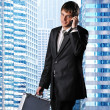 Young businessman against his office building — Stock Photo