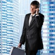 Stock Photo: Young businessman against his office building
