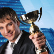 Happy businessman with a golden cup against his office building — Stock Photo