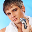 Handsome young man shaving — Stok fotoğraf
