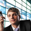 Young businessman with mobile phone over abstract background — Stock Photo