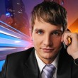 Royalty-Free Stock Photo: Young businessman talking on mobile phone against city background