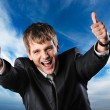 Happy businessman against blue sky — Stock Photo