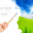 Hand with a brush painting blue sky and green grass — Stock Photo