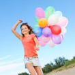 Happy girl with balloons running on the beach — Stock Photo #5311148