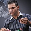 Portrait of a young gangster smoking and playing poker — Stock Photo