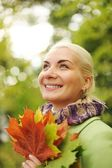 Woman with golden autumn leaves — Stockfoto