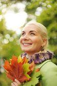 Vrouw met gouden herfstbladeren — Stockfoto