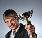 Happy businessman with a golden cup — Stock Photo
