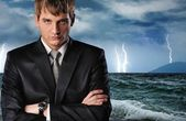 Seriour businessman over dark stormy sky — Stock Photo