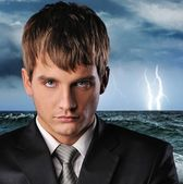 Portrait of a serious businessman over dark stormy sky — Stock Photo
