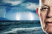 Elderly man's face over stormy ocean background — Stock Photo