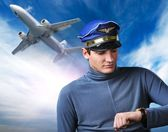 Handsome pilot against blue sky and flying plane — Zdjęcie stockowe