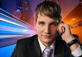 Young businessman talking on mobile phone against city background — Stock Photo