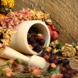 Wooden mortar, dog rose and dried flowers - Stock Photo