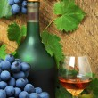 Stock Photo: Bottle, glass of cognac and bunch of grapes