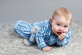 Adorável bebê deitado sobre um fundo cinza — Foto Stock