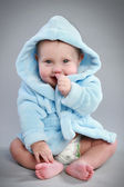 Charming baby in a blue bathrobe — Stock Photo
