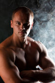 Young sporty man over Smoke. — Stock Photo