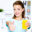 Woman thumbs-up with orange juice — Stock Photo #4036679