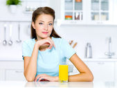 Woman with a glass of fresh orange juice — Stock Photo